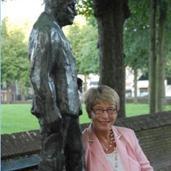 Trees Bruinsma bij het beeld van A. Roland Holst.