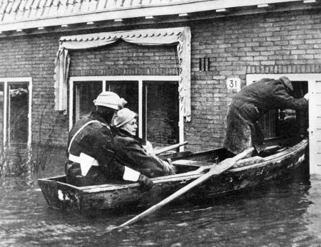 Evacuatie inwoonster Tuindop Oostzaan door motoragent te water, 14 januari 1960.