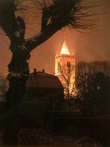 De verlichte toren bij nacht.