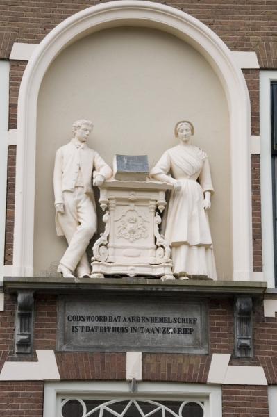 De beeldengroep op de gevel van het Oranje Weeshuis.