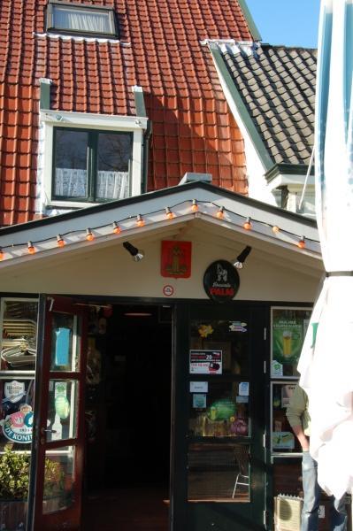 Het wapen van Huizen boven de ingang van het café.