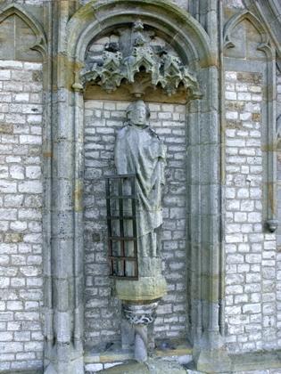 Beeld van Laurentius boven het grote venster in het zuidertransept van de Grote Kerk.
