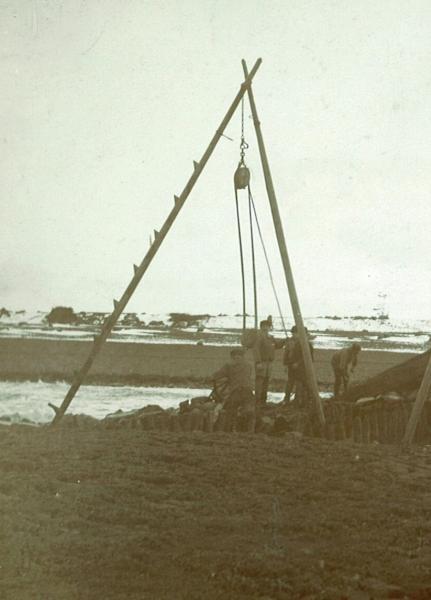 Dijkwerkers met driepoot hijsstelling, ca. 1930.