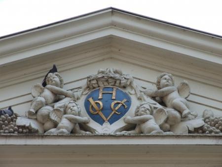 Het door vier putti vastgehouden schild met het monogram van de Hoornse Kamer van de VOC