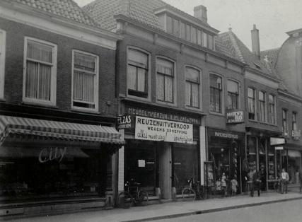 Rechts van meubelmagazijn Elzas is de kledingwinkel van firma E.W. Vet te zien.