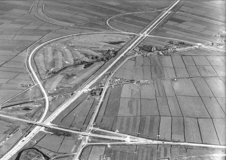 Verkeerswegen doorsnijden weilanden.