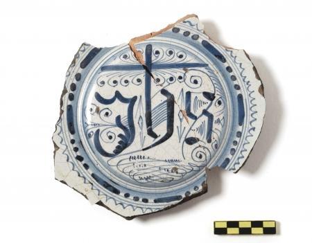 Een majolica pannenkoekschotel met het christelijke monogram IHS.