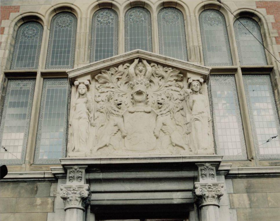 Gezag en Zachtmoedigheid flankeren het wapen van de koning aan de gevel van de Koninklijke Wachtkamer.