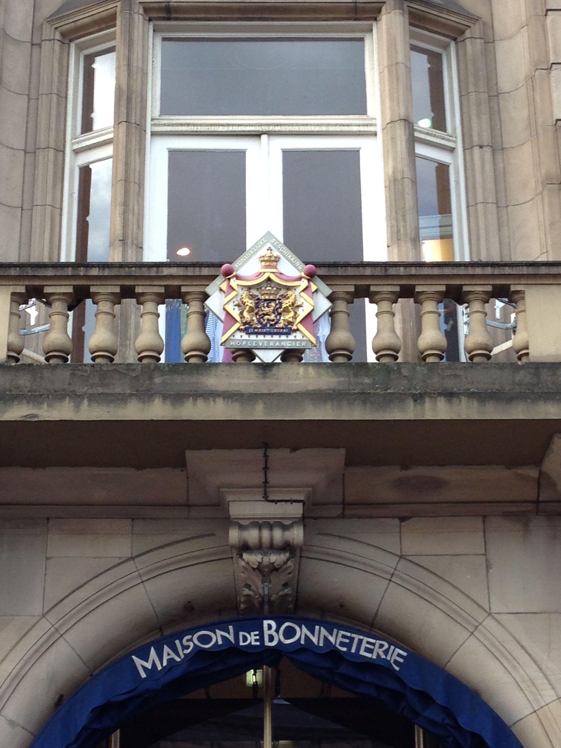 Het Hofleverancierswapenbordje aan de gevel van Maison de Bonneterie in Amsterdam