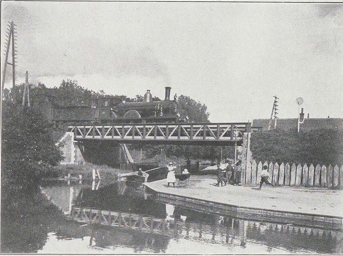 De HIJSM 369 op het spoorviaduct over de Brouwersvaart in Haarlem, rond 1900.