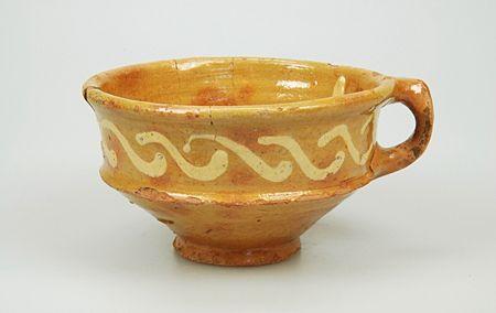 Kop van roodbakkend aardewerk met loodglazuur en slibversiering uit de periode 1675-1725.