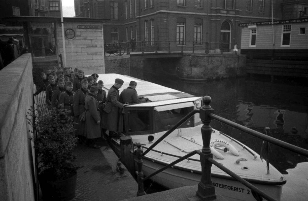 De Ordnungspolizei stapt in bij een rondvaartboot van Rederij Kooy aan het Rokin.
