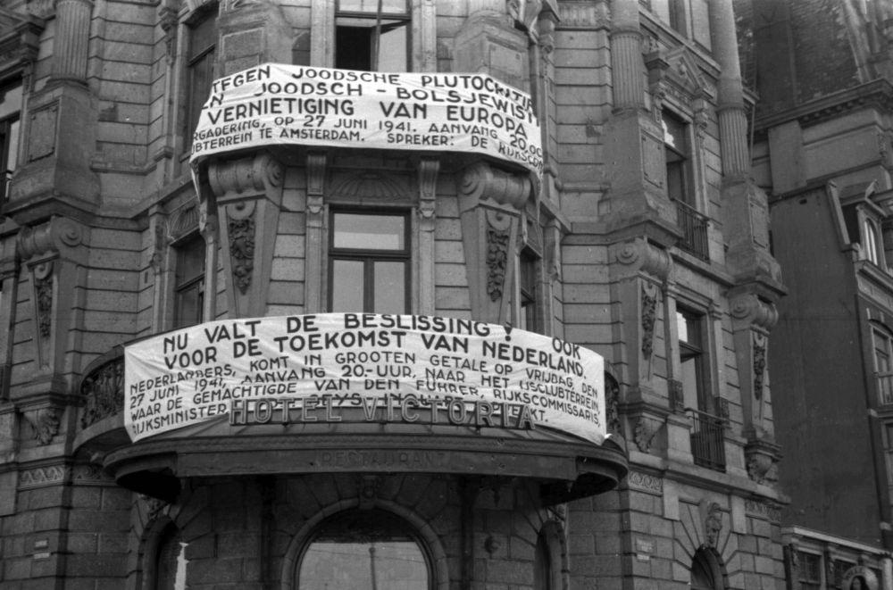 Nationaal-socialistisch spandoek aan het Victoriahotel op het Damrak.