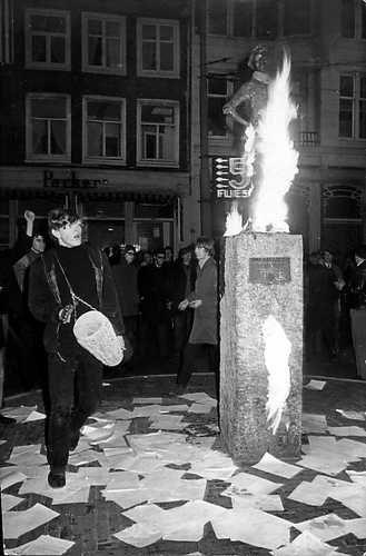 Provo's bij het Lieverdje op het Amsterdamse Spui, 20 maart 1966. Het beeld heeft een oranje sjerp om, is in brand gestoken. Er liggen vlugschriften op de grond en er wordt getrommeld. Voorwaar een happening