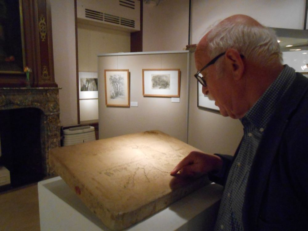 Peter Sluisman bij een steen, waarvan litho's worden gemaakt.
