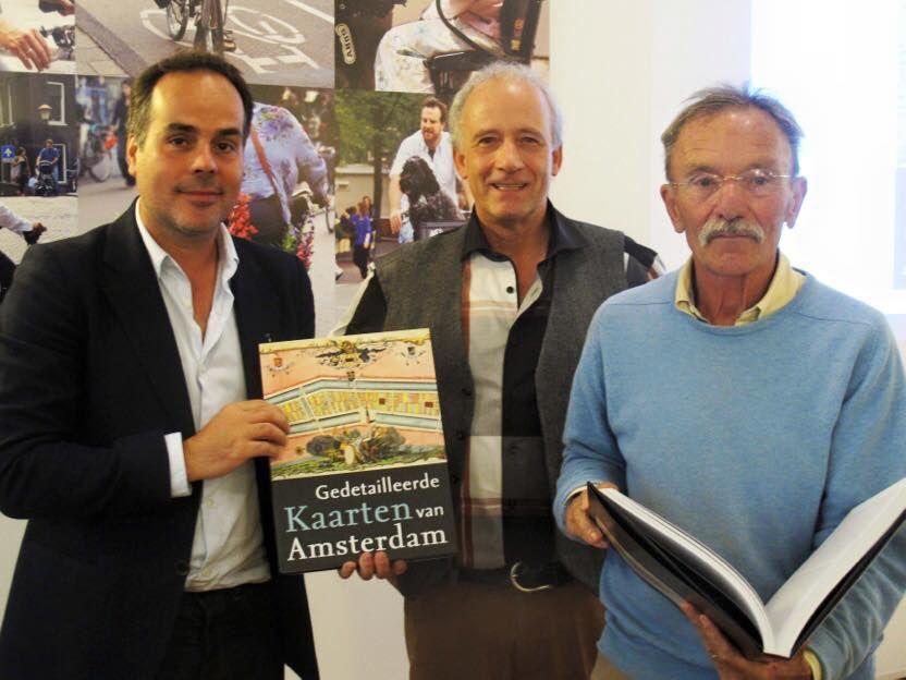 Auteur Marc Hameleers biedt zijn boek aan journalist John Jansen van Galen (r) en beeldend kunstenaar Jan Rothuizen (l), 2-10-2015