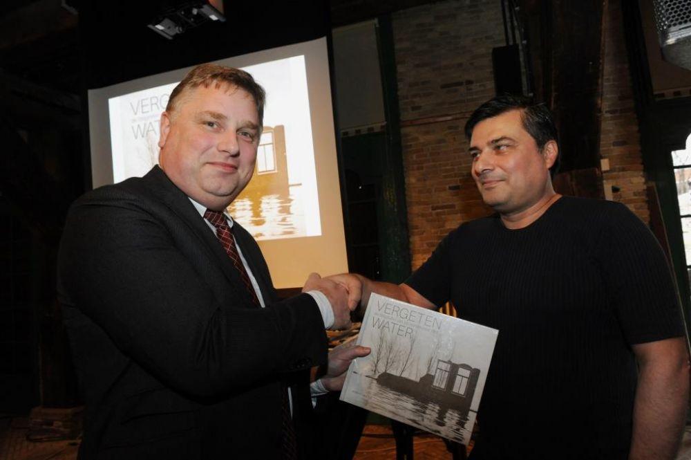 Gedeputeerde Cees Loggen neemt het eerste exemplaar in ontvangst van het boek 'Vergeten water'. Rechts auteur Jacques Laureys.