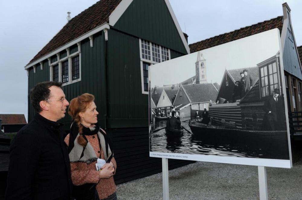 Bezoekers bekijken de foto die L.J. Karels maakte van kerkgang in Volendam, tijdens de watersnood.