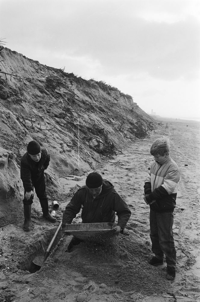 Strandjutters met een zeef