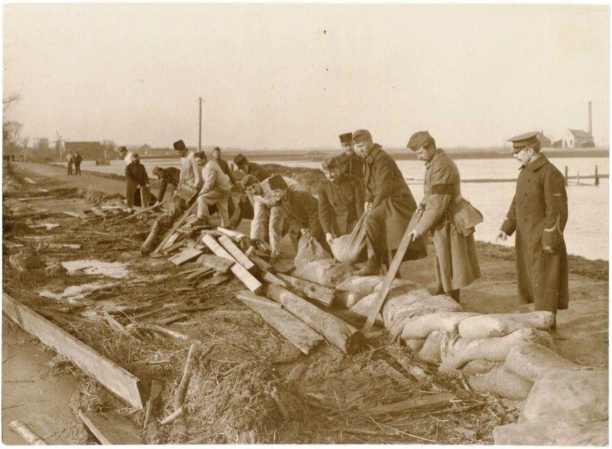 Purmerend, Purmersteenweg. Militairen leggen zandzakken langs de Where als bescherming tegen oeverafslag door het overstromingswater.