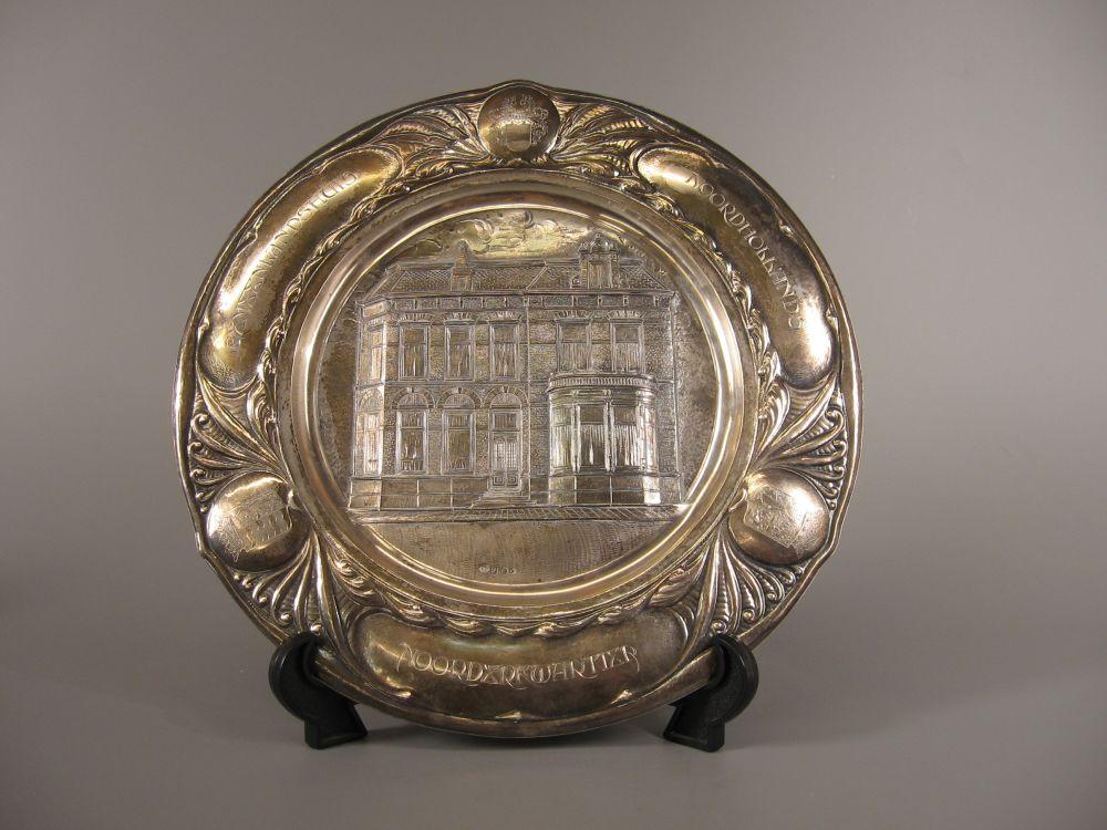 Het zilveren bord met daarop het kantoor van Hoogheemraadschap Noord-Hollands Noorderkwartier in Alkmaar, dat de eerste dijkgraaf C. Wijdenes Spaans bij zijn afscheid in 1936 cadeau kreeg.
