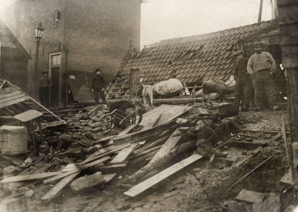 Door de overstromingen tijdens de watersnood is een huis volledig verwoest. Een paar mannen en jongens staan tussen de vernielde huisraad. Spakenburg, Nederland, 1916.