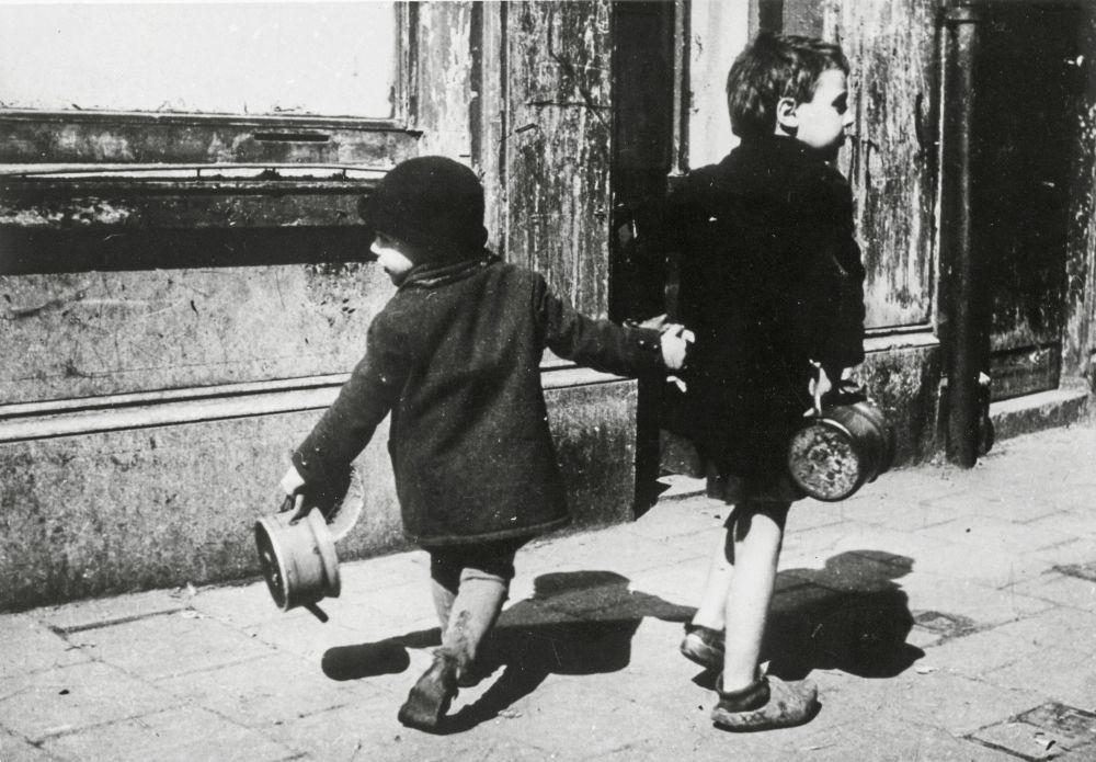 Twee kinderen zoeken eten in de hongerwinter.