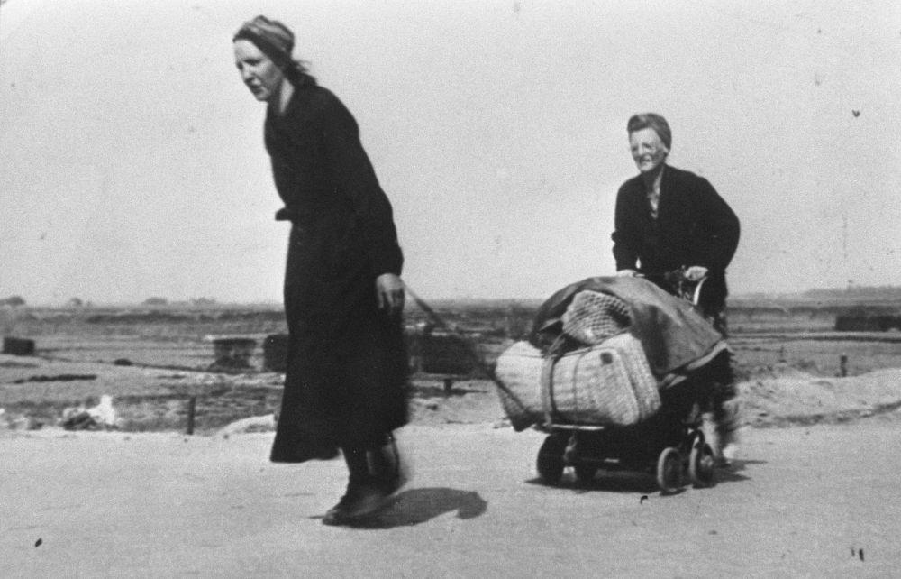 Twee vrouwen met een karretje bij elkaar gesprokkelde goederen.